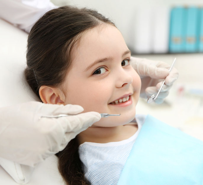 A smiling cute little girl having a dental a check up