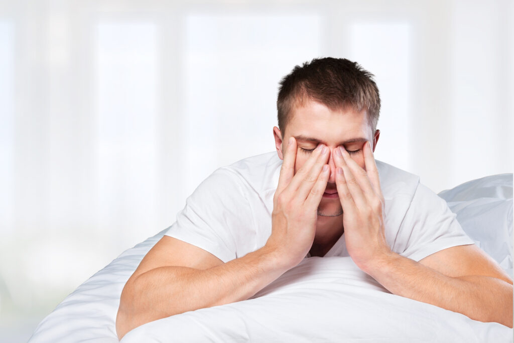 A picture of a man in bed holding her nose